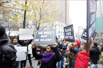 "demonstrators in New York holding placards, ""We Will Not Be Silent"", ""Black Lives Matter""."
