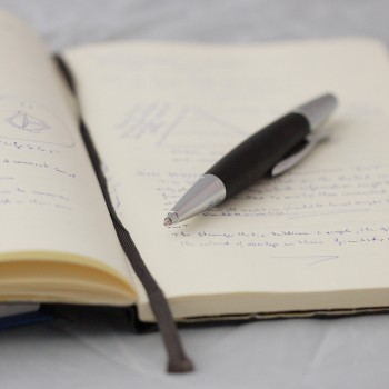 A pen resting on top of an open journal with writing faintly apparent.