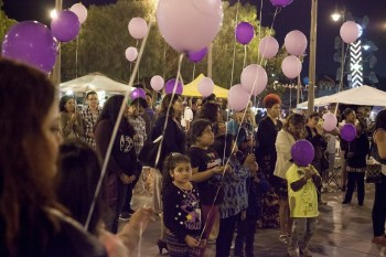 Children and Adults holding purple balloons