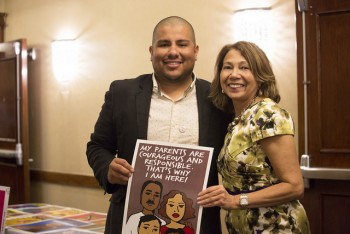 artist julio salgado with cal state fullerton president mildred garcia holding up poster for immigration reform