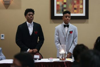 photo of two boys in formal dress facing audience at banquet