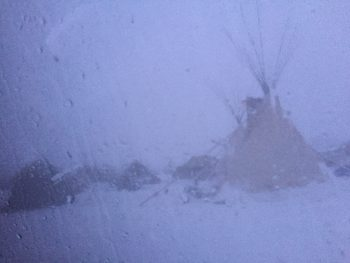 snow falling heavily over teepees and tents