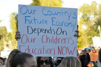 "sign says ""Our country's future economy depends on our children's education now"""